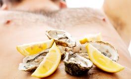 Austern auf man& x27; s-Bauch Lizenzfreies Stockfoto