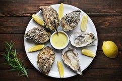 Austern mit Zitrone auf Platte Lizenzfreies Stockbild