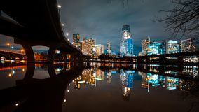 Austin skyline at night and Lamar pedestrial Bridge with bright illuminated buildings reflecting in Lady Bird Lake. Austin skyline at night and Lamar pedestrian royalty free stock images