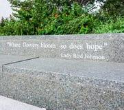 AUSTIN TEXAS SEPTEMBER 17, 2017: Citationstecken: `, var blommor blommar så, hoppas ` av damen Bird Johnson på en bänk utanför Ly Arkivbilder