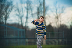Austistic Boy Pretending. Caucasian autistic boy in striped shirt pretends to throw a ball outside Royalty Free Stock Images