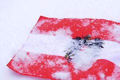 Austrain flag with Coat of Arms eagle covered in snow white background. Closeup Stock Images
