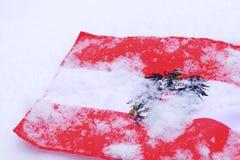 Austrain-Flagge mit dem Wappen Adler bedeckt im Schneeweißhintergrund Stockbilder
