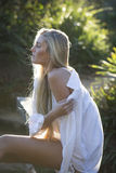 Australiër met Lange Blonde Haarzitting op Brug kijkt over haar Schouder Royalty-vrije Stock Afbeeldingen