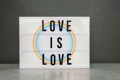 Light box with `love is love` and rainbow Royalty Free Stock Image