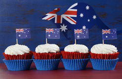 Australia Day cupcakes. Happy Australia Day January 26 party food with red velvet cupcakes with kangaroo flag on dark red and blue vintage rustic recycled wood Royalty Free Stock Photography