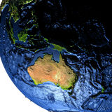 Australia on Earth at night with exaggerated mountains. Australia on model of Earth with exaggerated surface features including ocean floor. 3D illustration at Royalty Free Stock Photography