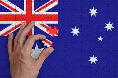 Australia flag is depicted on a puzzle, which the man`s hand completes to fold.  royalty free illustration