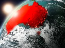 Australia on planet Earth in sunset. Australia during sunset highlighted in red on planet Earth with clouds and visible country borders. 3D illustration Royalty Free Stock Photo
