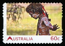 AUSTRALIA - postage stamp. AUSTRALIA - CIRCA 2011:A Cancelled postage stamp from Australia shows Aboriginal Boy, issued in 2011 royalty free stock image