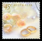 AUSTRALIA - Postage stamp. AUSTRALIA - CIRCA 1999: A Stamp printed in AUSTRALIA shows the Image for the Wedding rings with the yellow roses, Wedding series royalty free stock image