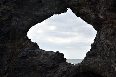 Australia rock and ocean in Narooma. The shape of Australia cut into the rock wall was accidental and was created when a ship was tied to the rock with large royalty free stock photography