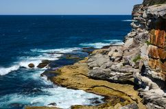 Waves crashing against rugged rock coastline at Lady Bay in South Head, NSW, Australia Stock Image