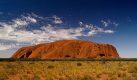 Australia's Uluru. Uluru, red rock under blue cloudy sky, bushland in front Stock Image
