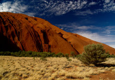 Australia's Uluru. Uluru, red rock under blue cloudy sky, bushland in front royalty free stock photography