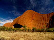 Australia's Uluru. Uluru, red rock under blue cloudy sky, bushland in front royalty free stock photo