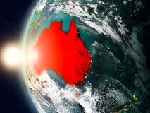 Australia during sunset on Earth. Satellite view of Australia highlighted in red on planet Earth with clouds and visible country borders during sunset. 3D Royalty Free Stock Images
