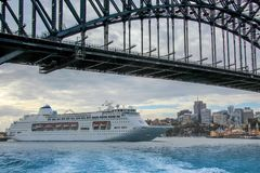 Cruise shipping under the Sydney Harbour Bridge. AUSTRALIA, SYDNEY - MARCH 21, 2014: Large cruise ship passing under the Sydney Harbour Bridge Stock Image