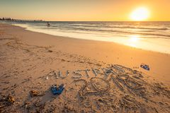 Australia text with thongs, flag and sunglasses on beach Royalty Free Stock Photo