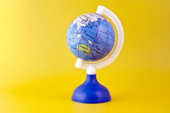 Australia on toy globe. Small toy globe with Australia and Atlantic Ocean isolated on yellow background Stock Photo