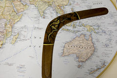Australia on world map with wooden boomerang. Australia on world map surrounded by wooden boomerang with indigenous art Royalty Free Stock Photos