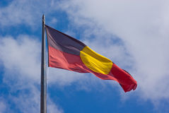 The Australian Aboriginal flag. The Official Australian Aboriginal flag against a cloudy sky Royalty Free Stock Photos