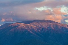 Australian Alps in orange sunset light and low clouds. stock photography