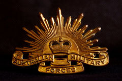 Australian army badge on black. 1960s era Australian Rising Sun army badge isolated on a black background Royalty Free Stock Image