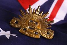 Australian army badge on flag. 1960s era Australian Army hat badge on an Australian flag background Stock Images