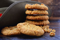 Australian Army Slouch Hat and Anzac Biscuits. Anzac Day Australian Army slouch hat with stack of traditional Anzac biscuits on dark vintage wood background Royalty Free Stock Photography
