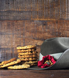 Australian army slouch hat and traditional Anzac biscuits on dark recycled wood. With remembrance red poppy for Anzac Day or Remembrance Armistice Day Royalty Free Stock Images