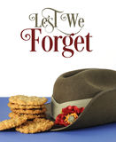 Australian army slouch hat and traditional Anzac biscuits with Lest We Forget text. Australian army slouch hat and traditional Anzac biscuits on white and blue Stock Photography