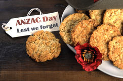 Australian army slouch hat and traditional Anzac biscuits with tag. Australian army slouch hat and traditional Anzac biscuits on dark recycled wood with Stock Image