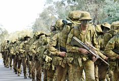 Australian army soldiers marching road to base in camouflage bush war tactics training