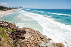 Australian beach during the day with rock cliff Stock Photos