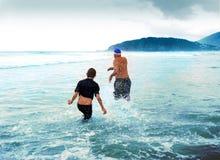 Australian Beach Fun Swimming. Man and boy running down the beach into the ocean. Boomerang Beach, New South Wales, Australia royalty free stock image