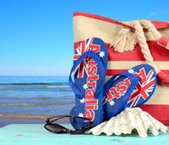 Australian beach scene with Aussie sandals. Beach bag, sunglasses and shell with view of blue ocean Royalty Free Stock Photography