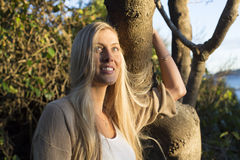 Australian Beauty with Long Blond Hair stands holding a tree. Royalty Free Stock Images