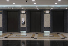Australian corporate lobby with elevators 2015. Clean, exclusive corporate interior with elevators and stone panelling. One elevator out of order Stock Images