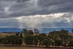 Australian countryside landscape. Sun rays protruding through storm clouds. Stock Image