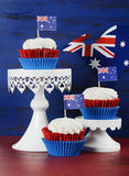 Australian cupcakes. Happy Australia Day January 26 party food with red velvet cupcakes with kangaroo flag on dark red and blue vintage rustic recycled wood Royalty Free Stock Images