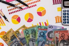 Australian dollar banknotes on business graphs with calculator and pen.  stock photography