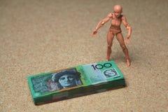 Australian 100 dollar bills. Stack of Australian 100 dollar bills with a generic figure standing next to it Stock Photography