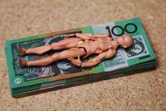 Australian 100 dollar bills. Stack of Australian 100 dollar bills with a generic figure lying on it stock image