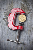 Australian Dollar Pressure Value. G-Clamp holding an Australian dollar coin on a wood background Royalty Free Stock Images
