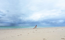 Australian fisherman sitting on deserted tropical island beach fishing. A young Australian fisherman is not going to be interrupted with his fishing, even with Royalty Free Stock Photos