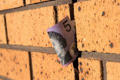 Australian five dollar note on wall. Selective focus. Australian money on wall. Five dollar bill in brick wall. Concept of money`s connection to building Stock Photography