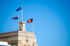 Australian flag and Aboriginal flag on the top of old clock tower building. An Australian flag and Aboriginal flag on the top of old clock tower building stock photography