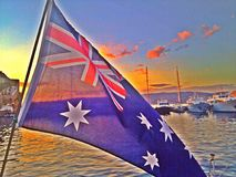 Australian flag. The Australian flag with boats and sunset in the background Royalty Free Stock Images