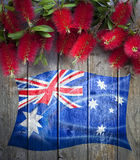 Australian Australia Day Flag Flowers Background. A rustic wood background with an australian flag and bottlebrush flowers royalty free stock image